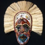 Tribal-style mask with large tan fibers representing hair, a dark brown face. The eyes have circles of black around them and the outside has a circle of blue as if the mask is wearing ceremonial paint.