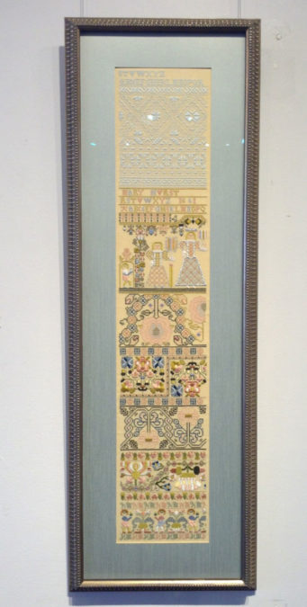 Antique embroidery sampler that has been matted and framed.