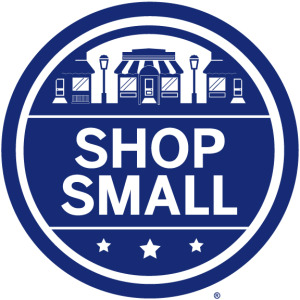 Round blue illustration of village above the words shop small