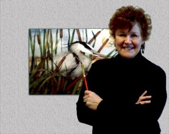 Photo of the artist standing in front of a painting of a heron.