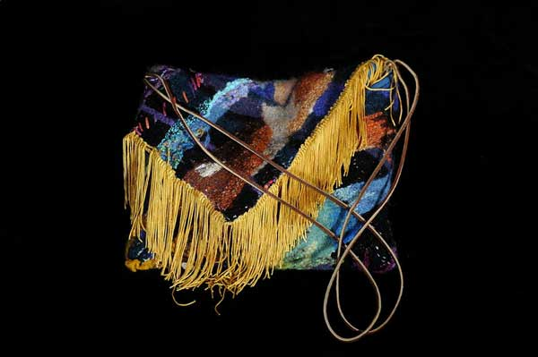 Purse made of colorful patchwork fabric and long, gold fringe on the closure flap.