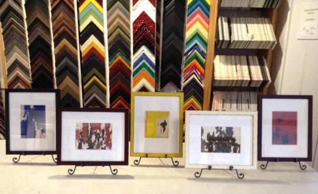 Five framed postcards lined up on framer's counter.