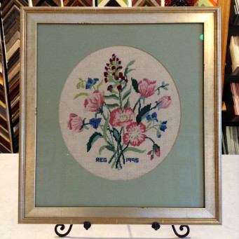 Colorful bouquet of embroidered flowers, matted and framed.