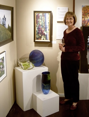 Photograph of Susan Koch standing next to an exhibit of her paintings.