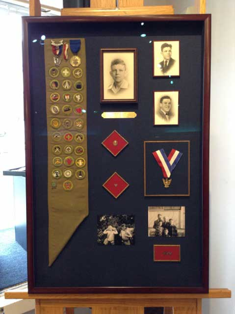 Shadow box full of scouting medals and old black and white pictures.