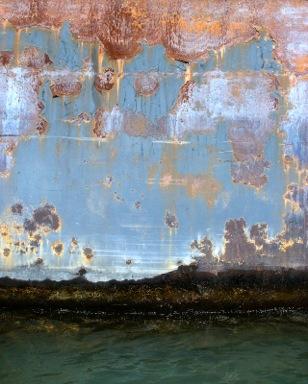 Encaustic painting with dark land or water beneath blue sky