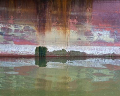Encaustic painting with city surrounded by water and rusty sky above