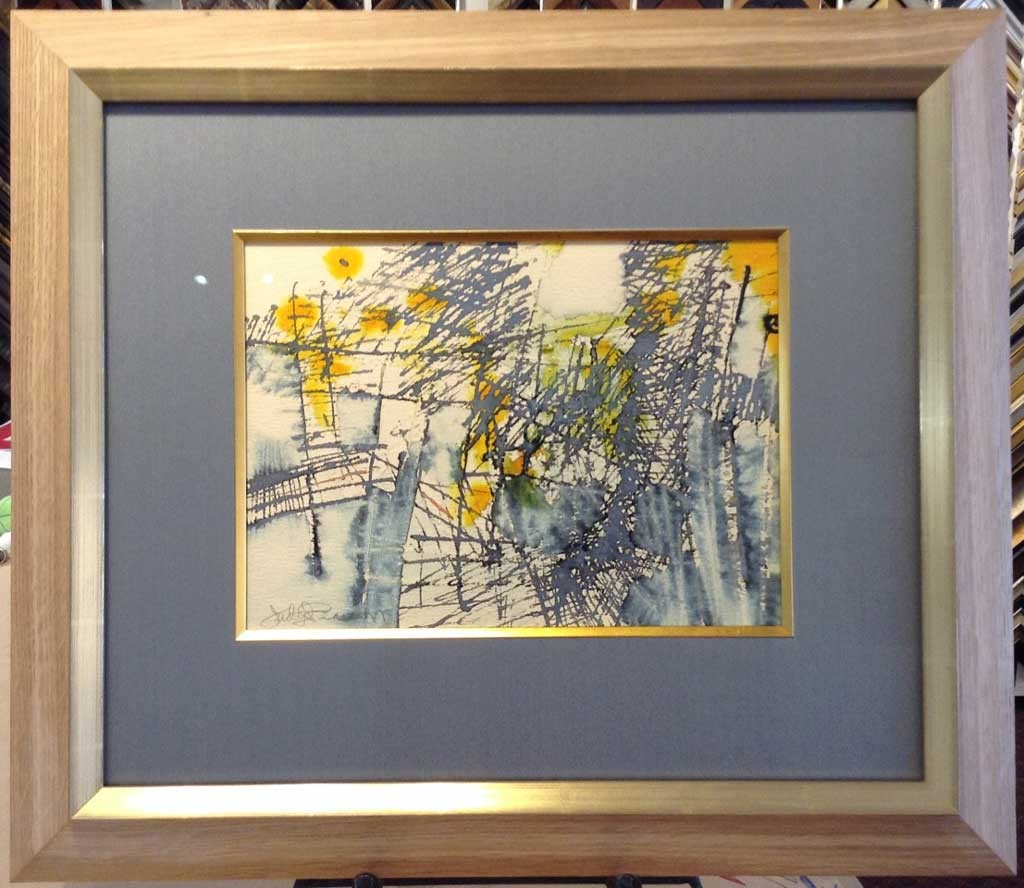 The artwork with new wooden frame and gray blue matting.