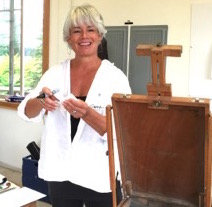 Artist Carrie Moore in front of an easel in her studio