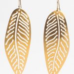 Gold earrings in the shape of a leaf.