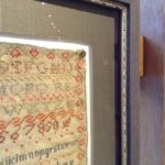 Close up of antique sampler framed behind glass.