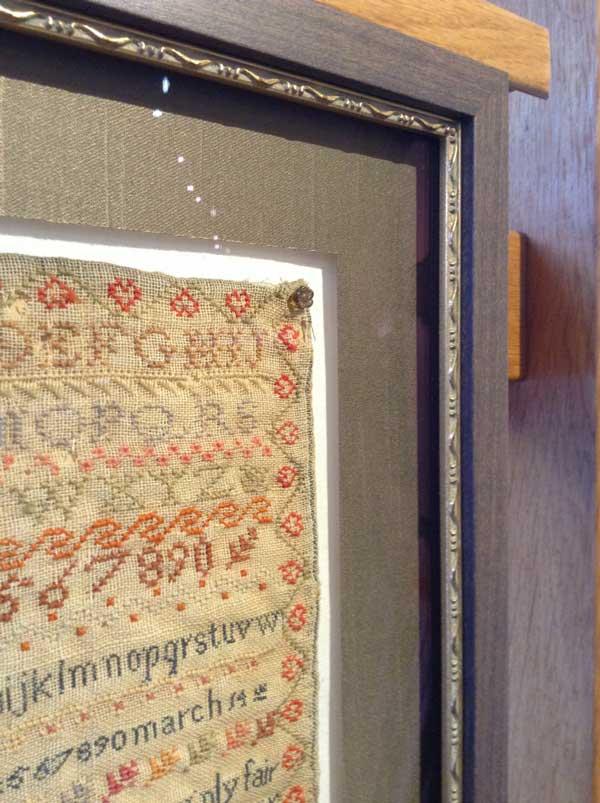 Close up of antique sampler framed behind glass.