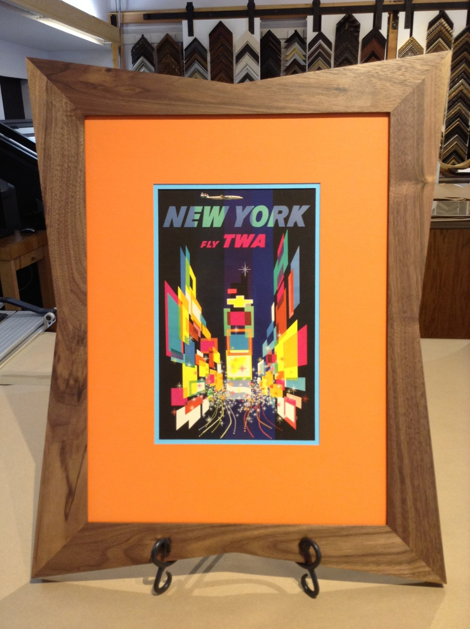 Colorful vintage TWA advertisement framed in mid-century modern wood frame and orange matting