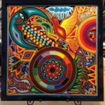 Brightly colored string art image of sun, moon, medicine wheel, maize, birds, and animals