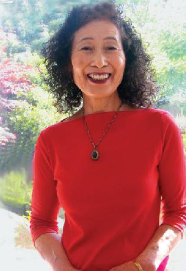 Noriko Hirayama, smiling broadly, standing in front of colorful trees.